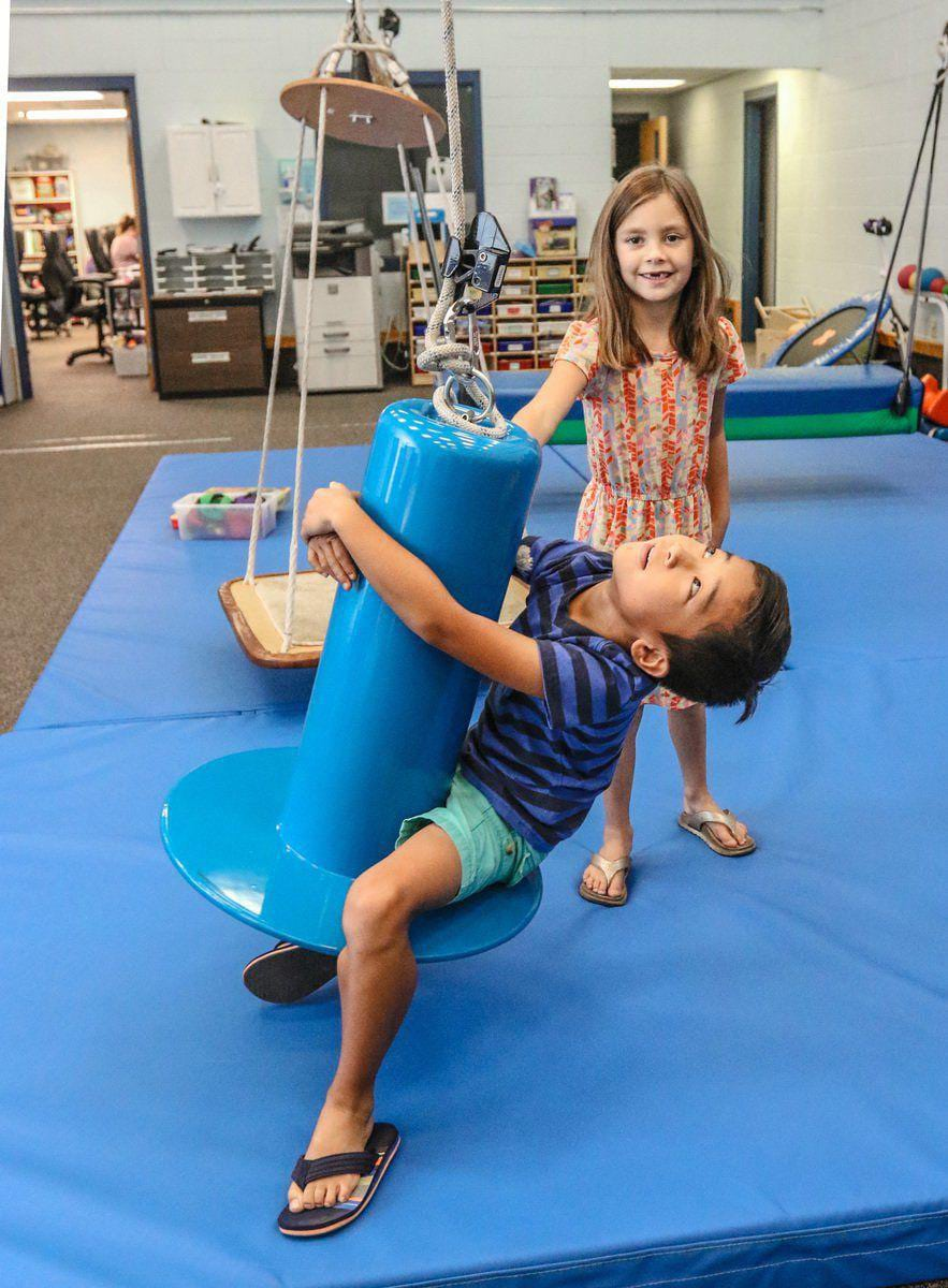 Two children playing in an occupational therapy gym